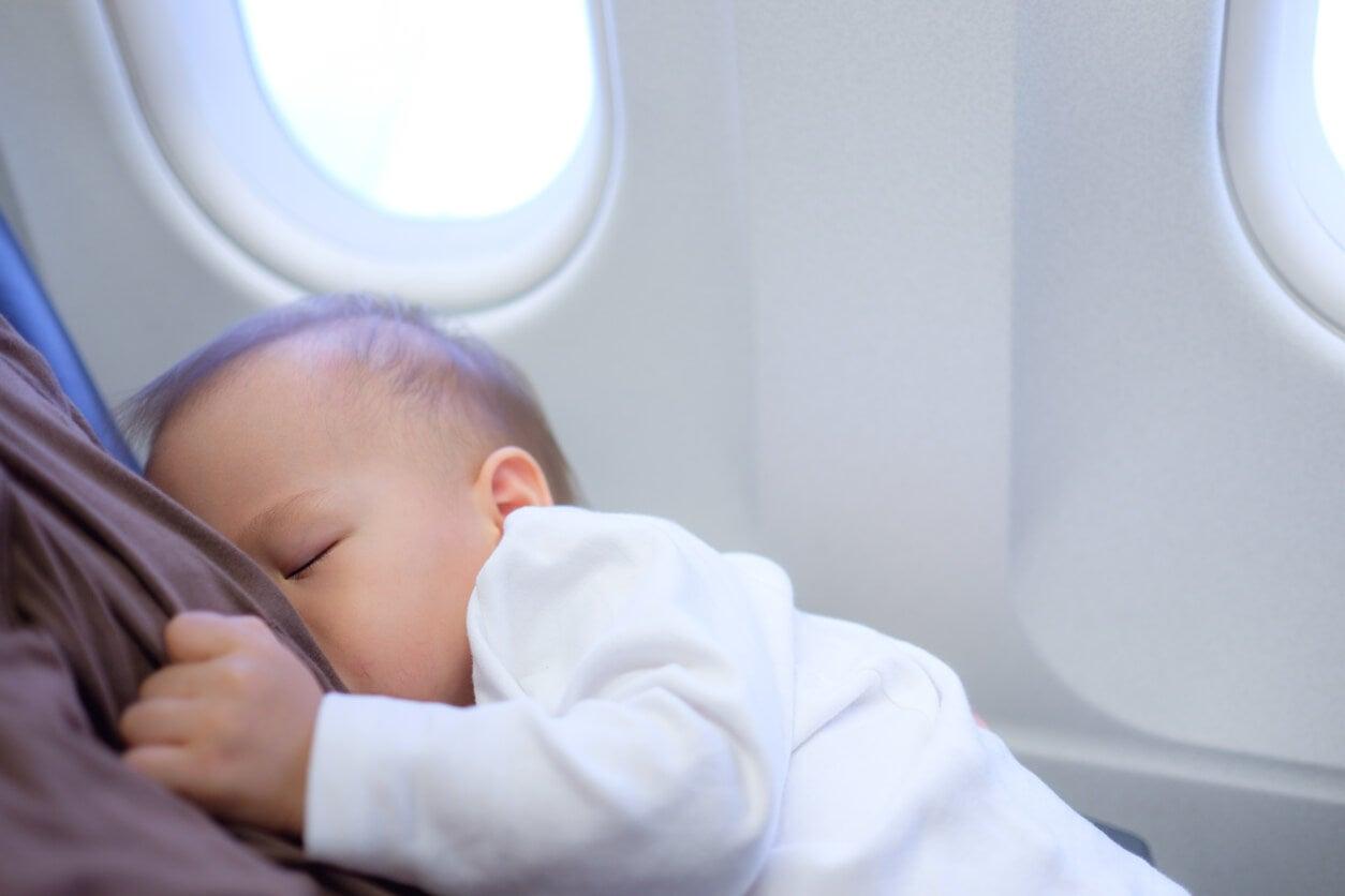 Un bébé qui tète le sein de sa mère dans un avion.