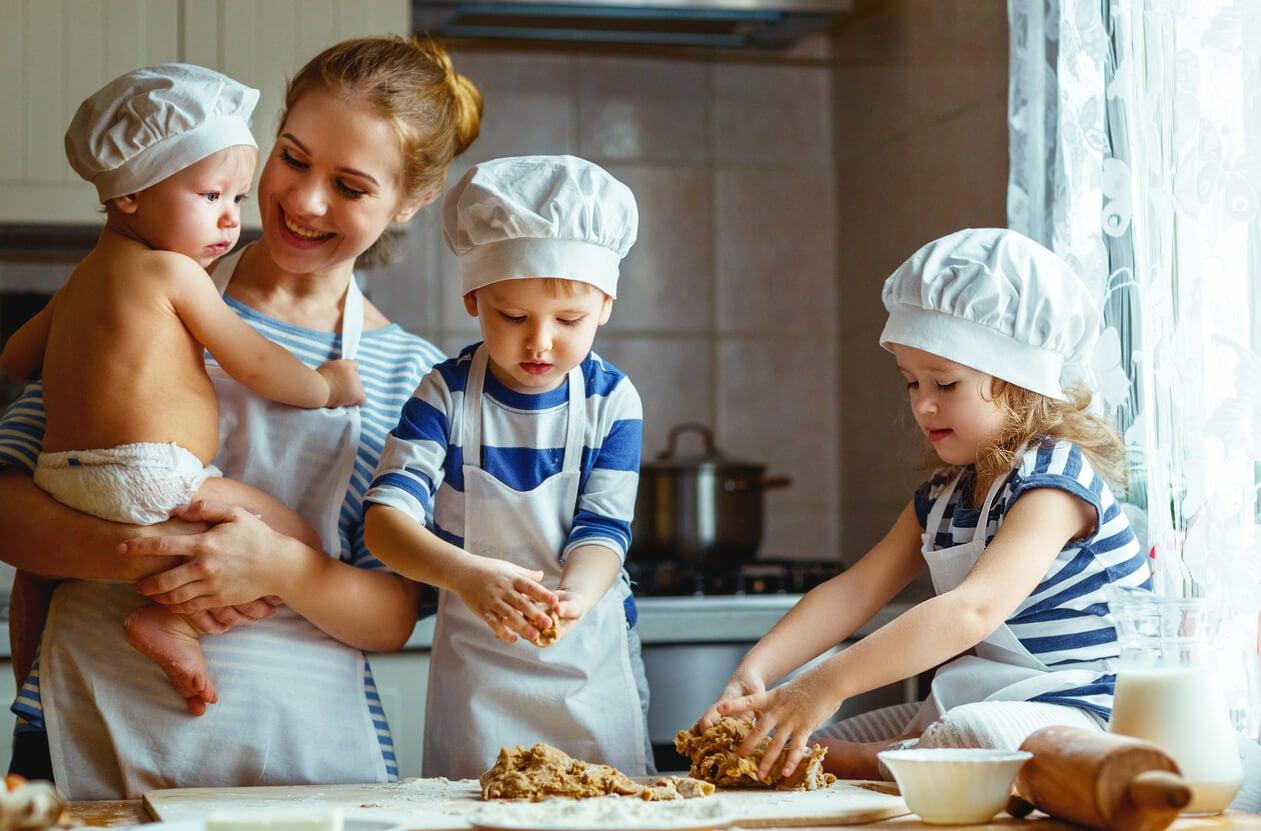 madre seno bambino ragazza bambino bambini impastare pasta biscotto tavolo da cucina controsoffitto tavolo farina cappello da cuoco giorno pomeriggio felice condivisione incoraggiamento abitudine sana