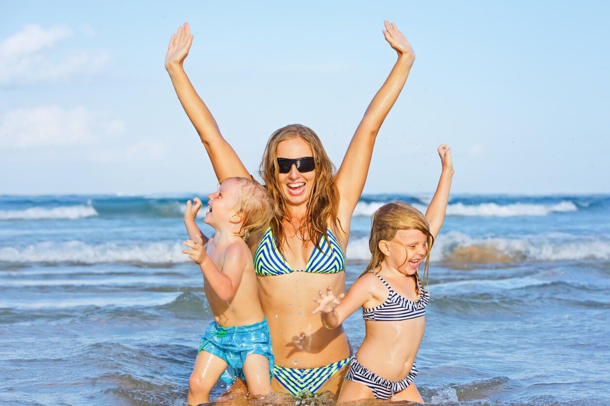 mamma bambini bebè bebè gemelli felici fratelli spiaggia giorno di maggio sole vacanze estive costumi da bagno
