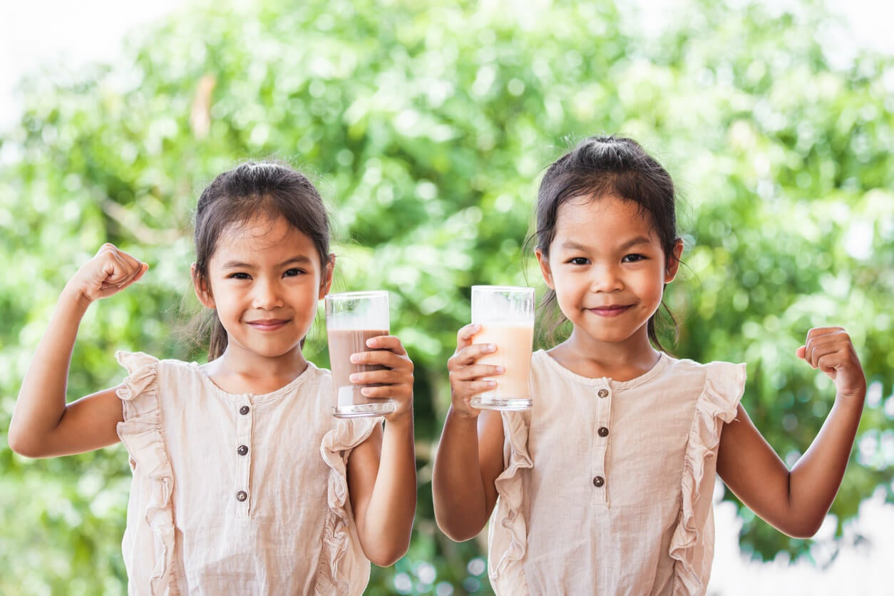 Deux jeunes filles qui boivent une boisson chocolatée.