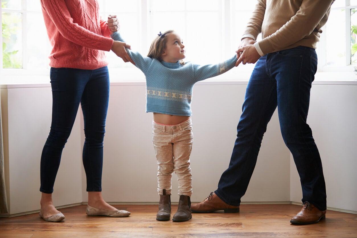 Une jeune fille prise par les bras par ses deux parents.