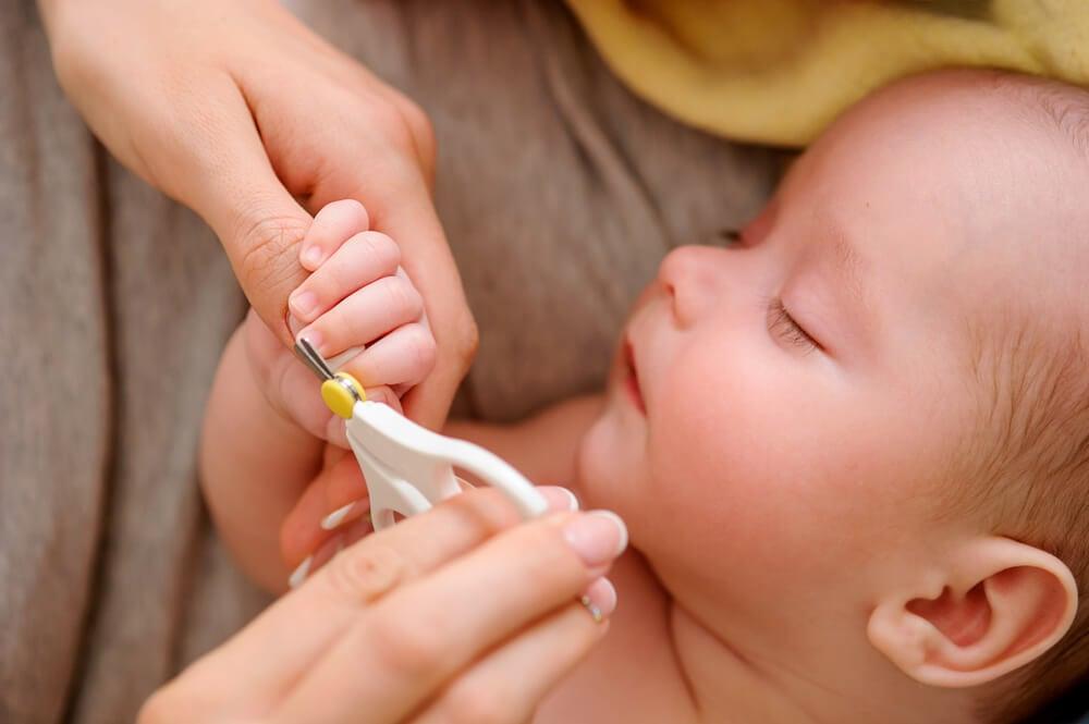 Maman coupant les ongles du bébé.