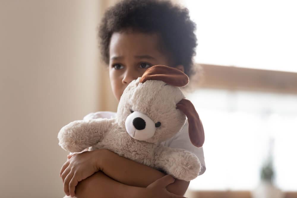 Un enfant avec une peluche dans les bras.