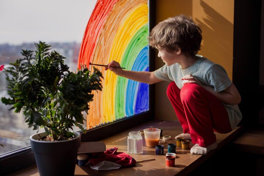Un enfant qui dessine un arc-en-ciel sur une fenêtre.