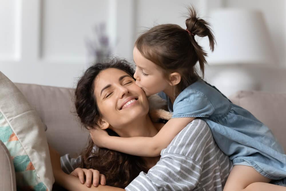 Une jeune fille qui fait un baiser à sa maman.