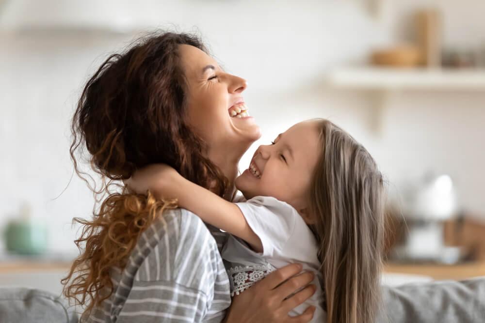 Une mère et une fille qui échangent un câlin.