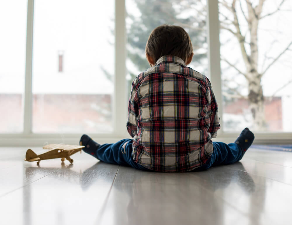 Un enfant assis devant une fenêtre.