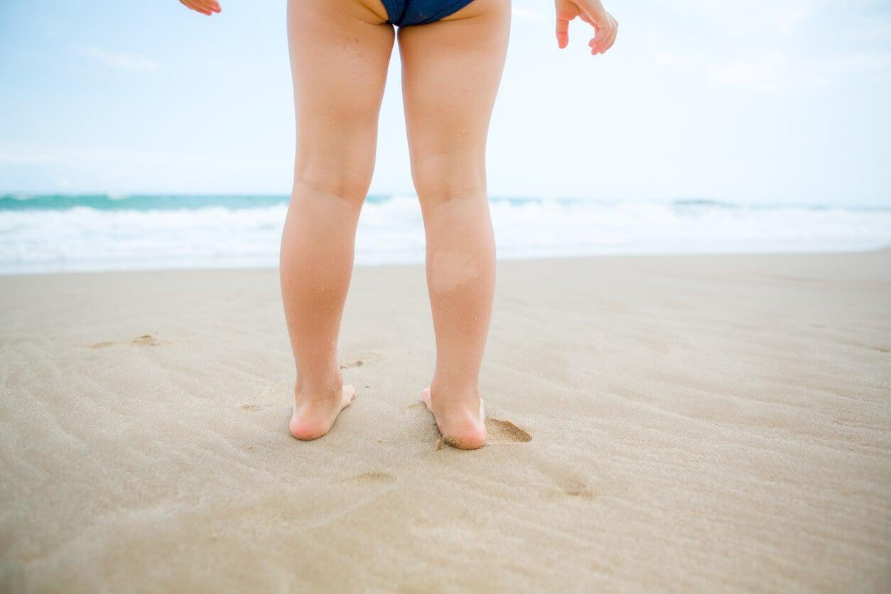 Les jambes d'une jeune fille sur la plage.