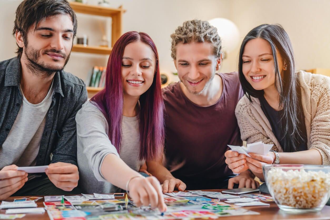 grupo amigos adolescentes juegan juego mesa turnos diversion