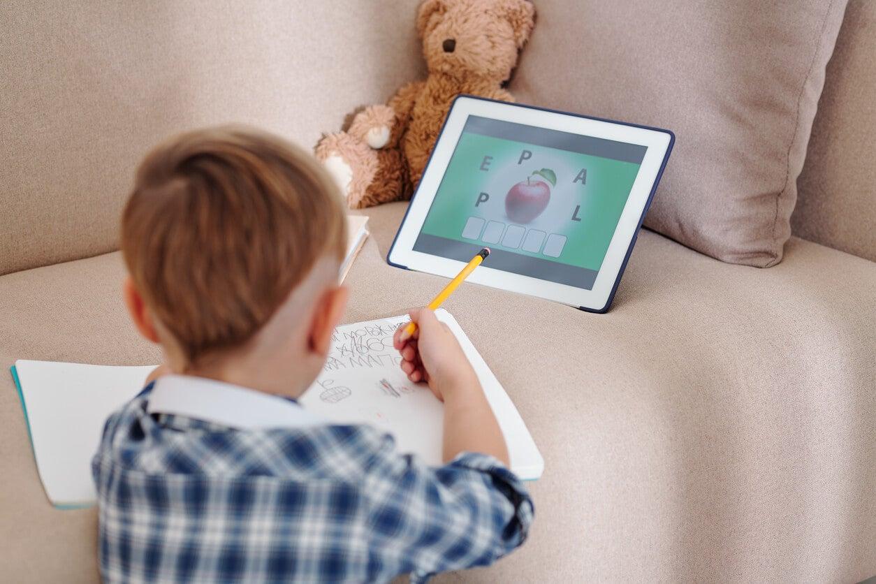 nino escolar aprende lenguaje escritura lectura en casa sillon tablt oso de felpa cuaderno lapiz escribe copia