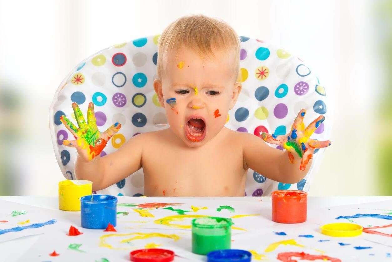 Un enfant qui peint avec ses doigts.