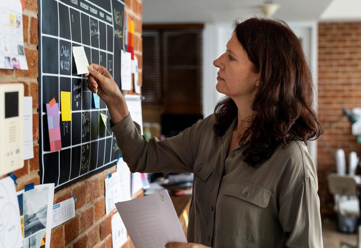 mujer madre organiza tareas calendario pegatinas recordatorios