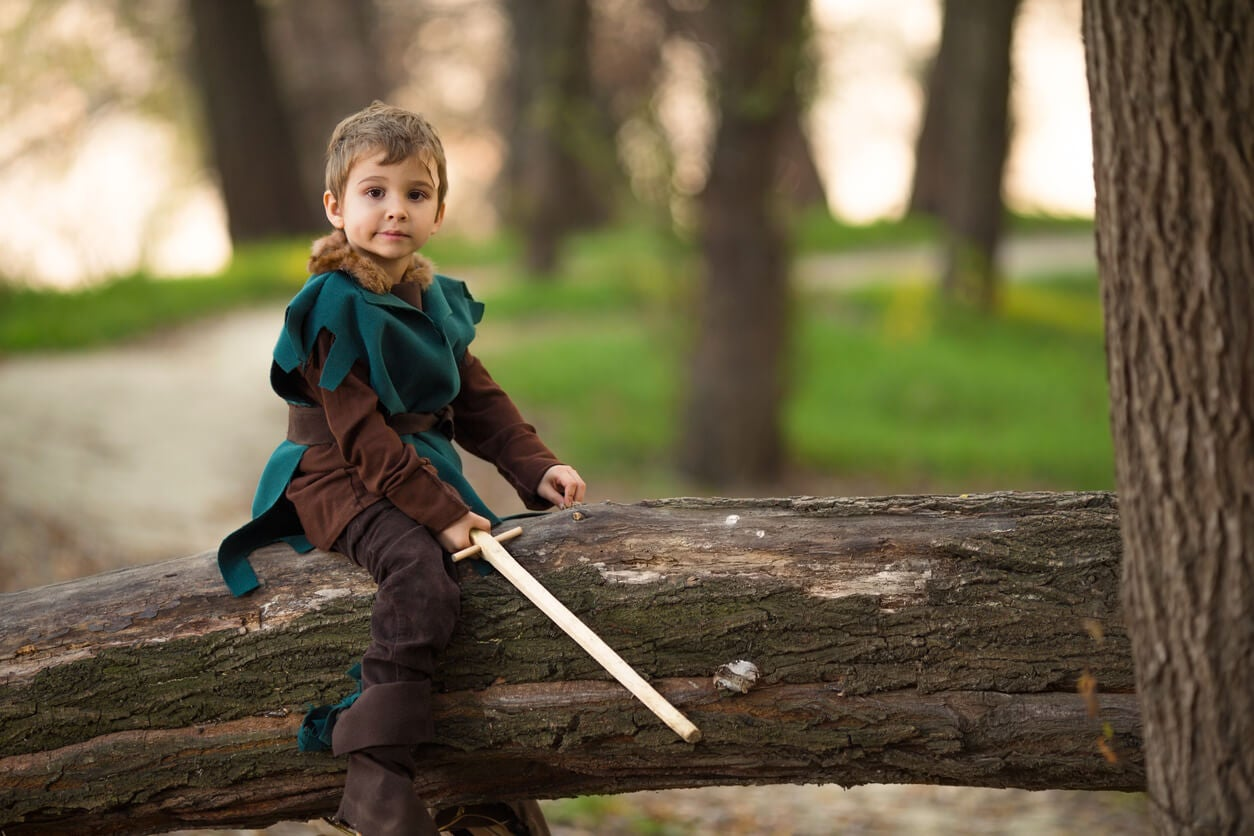 nino disfrazado hombre medieval edad media espada arbol