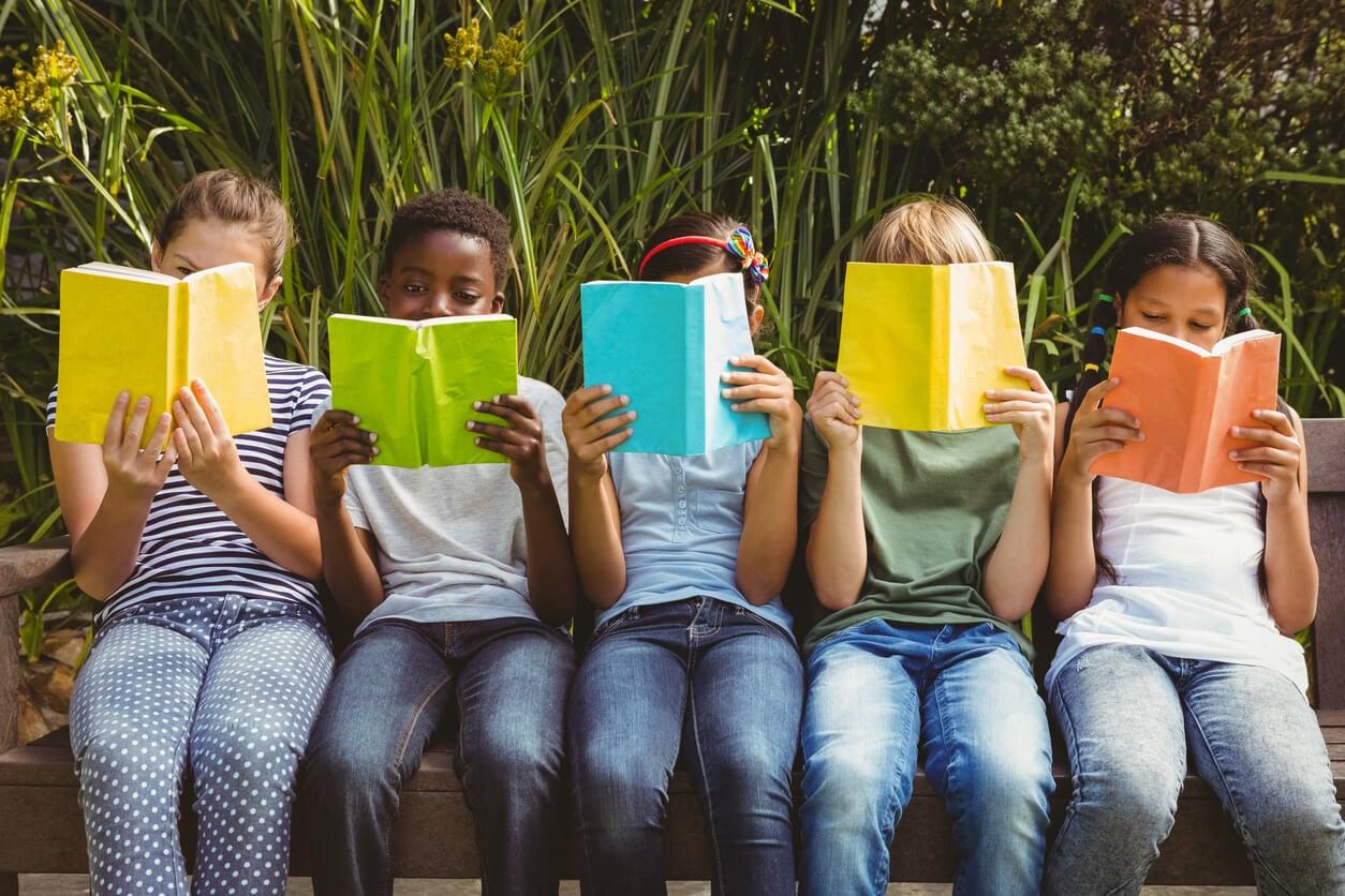 ninos sentados leyendo leen parque libros colores lectura compartida
