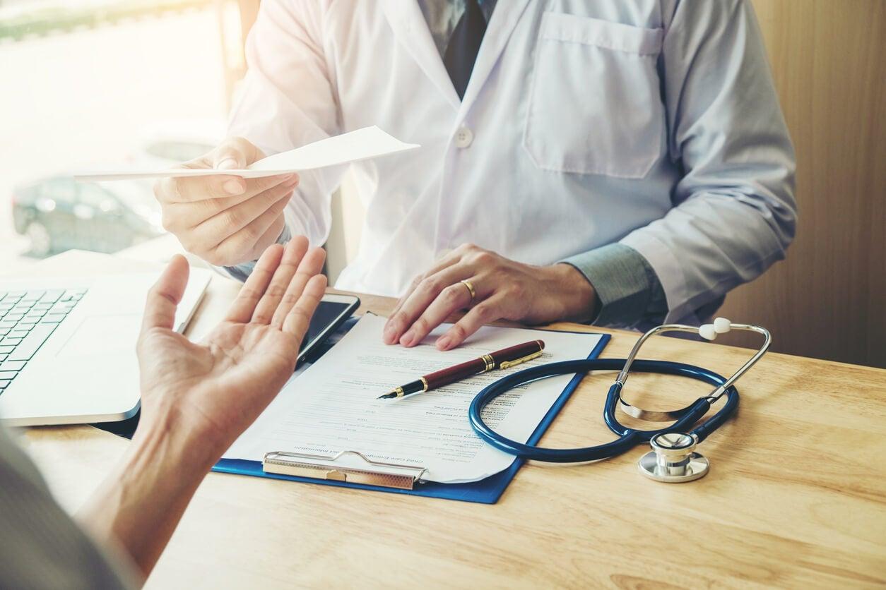 medico prescribe receta medica entrega en mano a paciente femenina mujer
