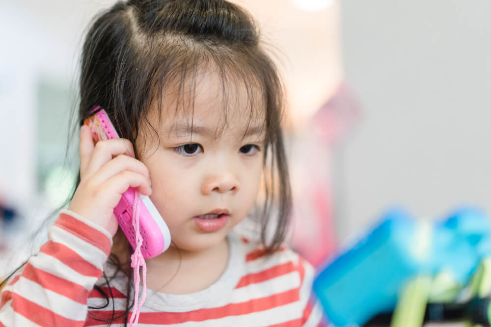 Niño habla solo por teléfono.