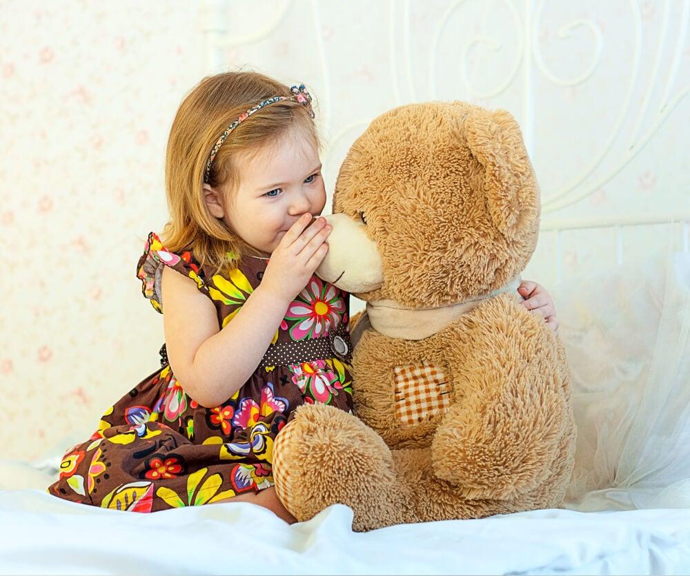 Niño habla solo junto a su oso.