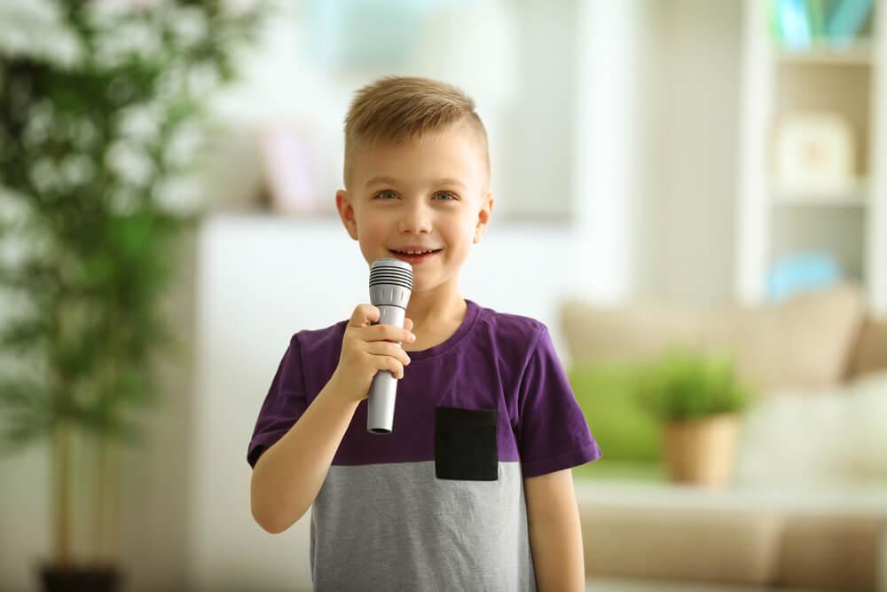 Niño hablando solo mientras juega con un micrófono.