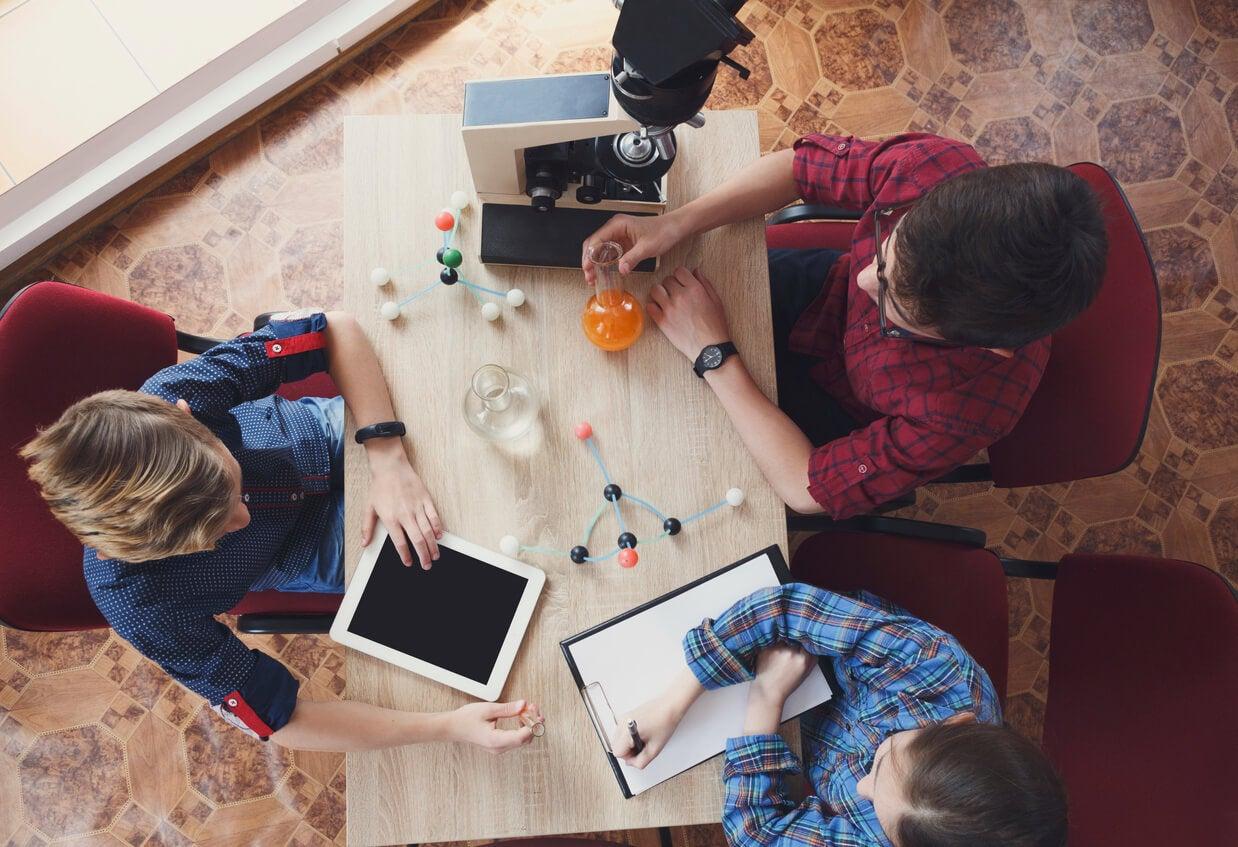 adolescentes en la mesa estudian quimica moderna table cuaderno probeta tubos atomos moleculas modelos