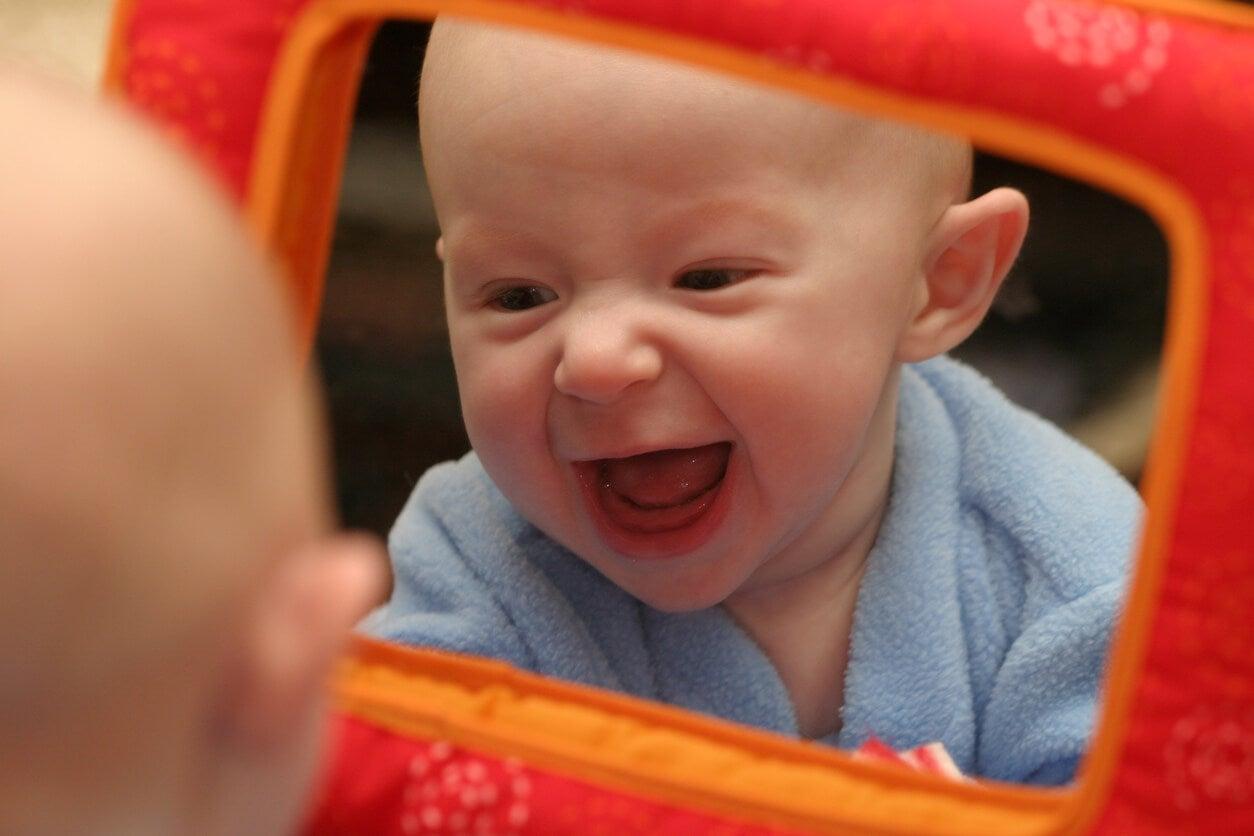 bebe se rie frente al espejo reflejo