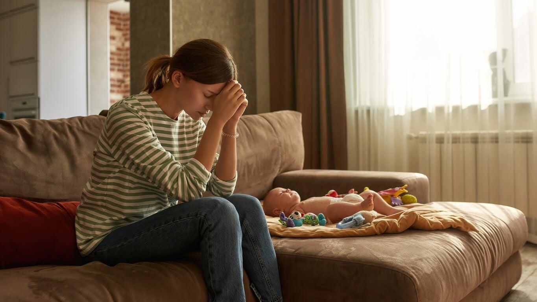 mama deprimida preocupada desolada junto a bebe solo en el sofa sillon
