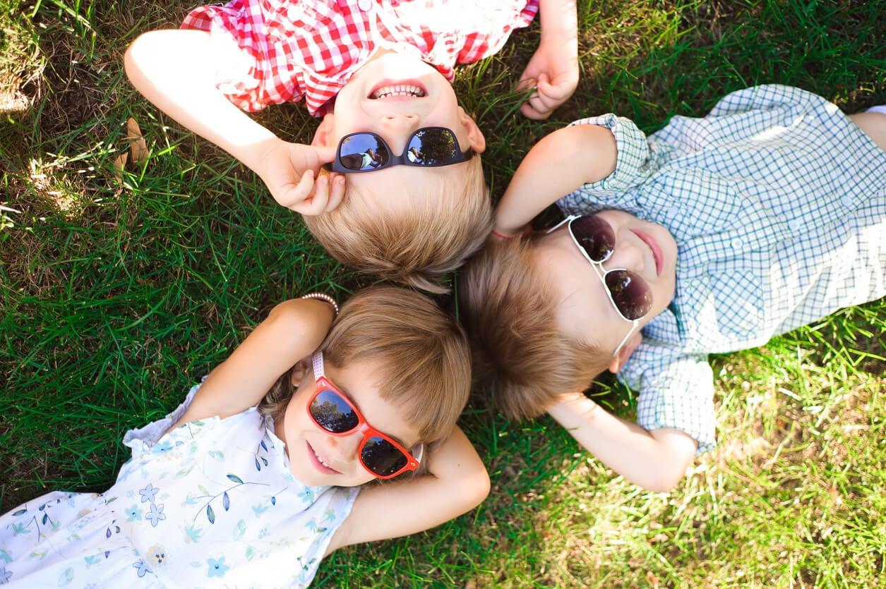 ninos al aire libre acostados en pasto felices gafas sol oscuras fotoproteccion