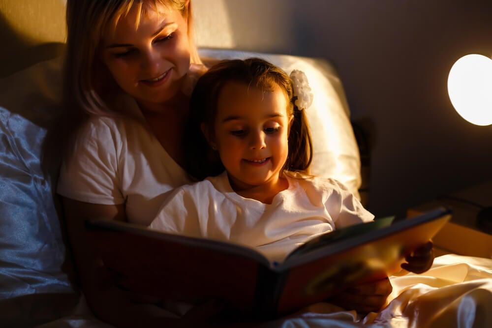 Hija disfrutando de un libro antes de dormirr